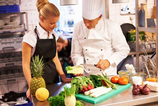 Portrait of experienced chef giving culinary lessons to female trainees